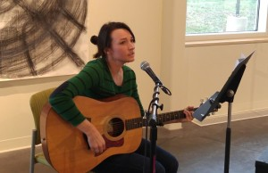 MFA Art Therapy student Sarah pray performs acoustic music during the opening of the annual Art Therapy Exhibit. (Photo by Joseph Lacdan)