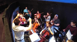 Professor Marc Schapman leads the student orchestra during rehearsals. (Photo by Joseph Lacdan)