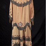 """Anishinaabe """"tinkle cone"""" dress, c. 1930. The garment was originally bright red and features dentallium shells, glass beads, metal conches and the cones, hand-made from rolled tin cans. The red labeling of the cans can be seen from inside the cones. Photo courtesy of Mark Proudfoot."""